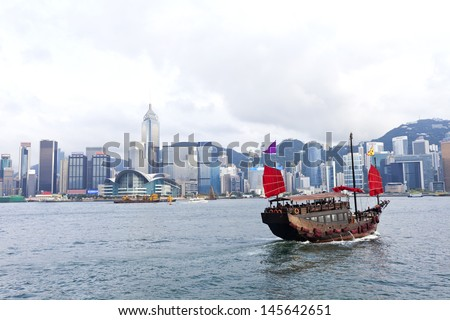 Hong Kong harbor with tourist junk boat - stock photo