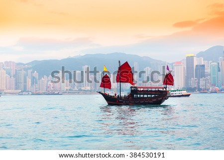 Hong Kong harbour with tourist junk in evening - stock photo