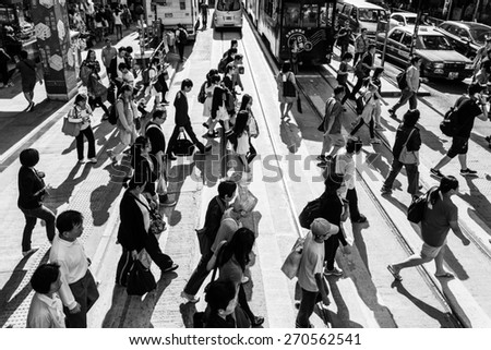 Hong Kong, Hong Kong - April 17 2015: People cross a street in Hong Kong island central district. Captured in black and white with a strong contrast. - stock photo