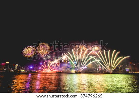 Hong Kong, Hong Kong - January 1 2016: Fireworks illuminate the sky above the famous Hong Kong skyline as viewed from Kowloon across the Victoria Harbor for New Years day. - stock photo