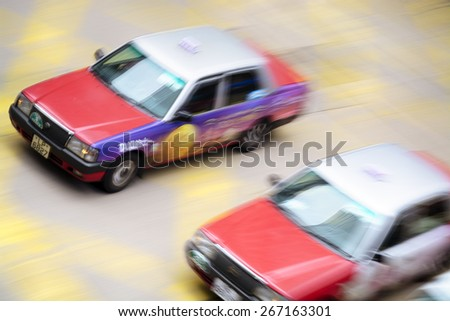 Hong Kong, Hong Kong SAR -November 14, 2014: Motion blurred Taxis in Hong Kong. Taxis of Hong Kong provide a taxi system. Most taxis are independently owned and operated. - stock photo