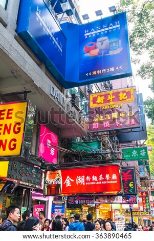 HONG KONG - JAN 18, 2015: Hong Kong cityscape view with plenty bright advertisements and billboards. People walking at crowded streets with skyscrapers and shopping malls