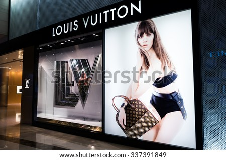 HONG KONG - 22 JAN, 2015: Louis Vuitton boutique display window with mannequin in luxury clothes and accessories for exclusive shopping. French fashion house founded in 1854 by Louis Vuitton - stock photo