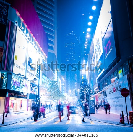 HONG KONG - JAN 16, 2015: Night view of modern city  street with illuminated shopping malls, skyscrapers, cars and walking people. - stock photo