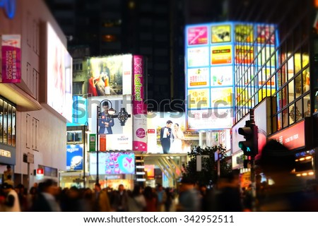 HONG KONG - JAN 16, 2015: Tilt shift blur effect. Night view of big sopping mall with bright illuminated banners and people walking on crossroad at crowded city. Hong Kong