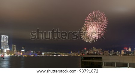 HONG KONG - JANUARY 24: Fireworks light up the night sky over Victoria Harbor to celebrate the Chinese New Year (year of the dragon) on January 24, 2012 in Hong Kong. - stock photo