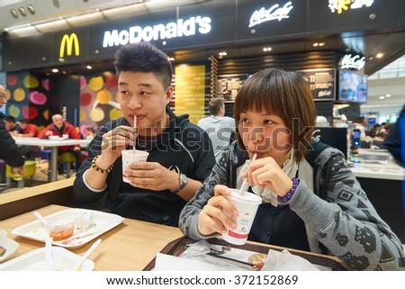 HONG KONG - JANUARY 29, 2016: people eat in McDonald's restaurant. McDonald's primarily sells hamburgers, cheeseburgers, chicken, french fries, breakfast items, soft drinks, milkshakes, and desserts - stock photo