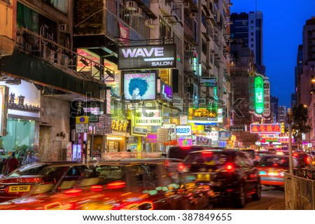 HONG KONG - JULY 27: Cars streak along busy Sai Yeung Choi Street in Mongkok, Kowloon, as colorful billboards light up the area at night July 27, 2015. The area is famous for shopping and eating. - stock photo