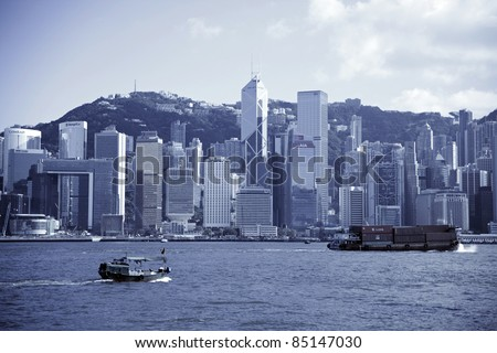 HONG KONG - JULY 5 : Ferry cruising Victoria harbor with Hong Kong skyline in the background on July 5, 2011 in Hong Kong, China. The ferry company has been in operation for more than 120 years. - stock photo