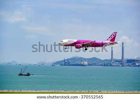 HONG KONG - JUNE 04, 2015: Peach aircraft landing at Hong Kong airport. Peach Aviation, operating under the brand name Peach is a low-cost airline based in Japan - stock photo