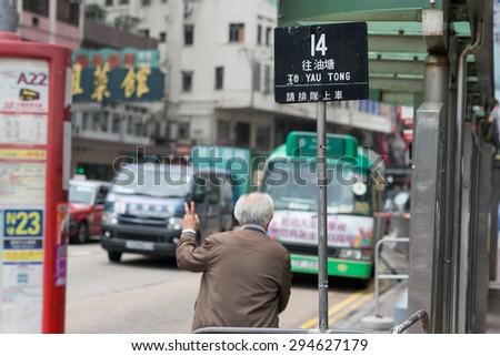HONG KONG - MAR 30 : old man waving a bus at the bus stop on Mar 30,2015 in HONG KONG - stock photo