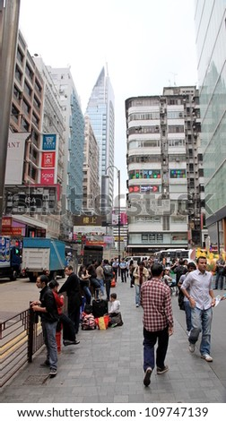 HONG KONG - MARCH 30: A busy street on March 30, 2012 in Hong Kong. With a land mass of 1,104 km2 and a population of 7 million people Hong Kong is one of the most densely populated areas in the world - stock photo