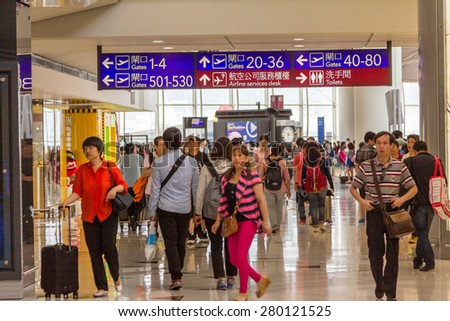 HONG KONG - MAY 03, 2015: Passengers are rushing to their departure gates in Hong Kong international airport. About 90 airlines operate flights from HKIA to over 150 cities across the globe. - stock photo