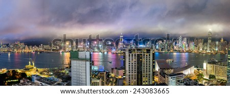 HONG KONG - MAY 12, 2014: Stunning panoramic night view of Hong Kong Island and Kowloon on a cloudy day from tower roof. Last year HK hosted more than 54 million visitors, most from the mainland. - stock photo