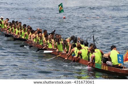 HONG KONG - MAY 25, 2014: Unidentified team competes at the 2014 Dragon Boat Race to celebrate the Tuen Ng festival at Chai Wan bay on May 25, 2014 in Hong Kong. - stock photo