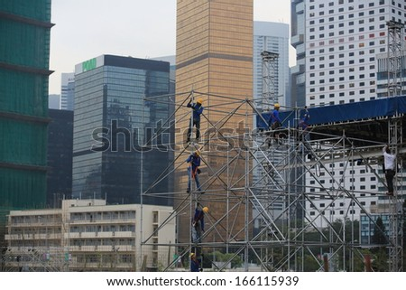 HONG KONG NOVEMBER 30: the unidentified workers are scaffolding on the site in the city surrounding by skyscrapers in Central on 30 nov 2013. Oversea labors are welcomed to HK as the shortage. - stock photo