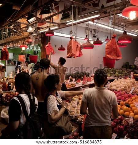 HONG KONG - October 2016: People shopping at fruit stall on wet market.