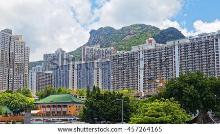 hong kong public estate with landmark lion rock at day - stock photo