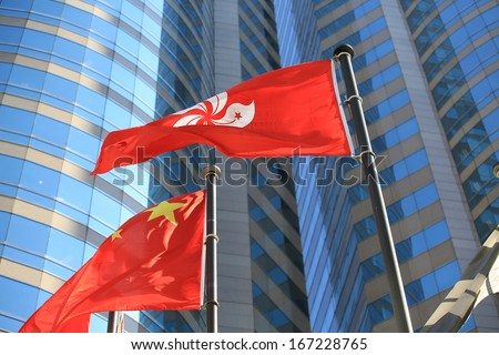hong kong regional flag and China flag in the wind with building background - stock photo