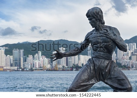 HONG KONG - SEPT. 13 : Bruce Lee statue on the Avenue of Stars on Sept 13, 2013 in Tsim Sha Tsui, Hong Kong. The statue is one of the main attractions on the famous waterfront promenade.  - stock photo