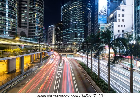 HONG KONG - SEPTEMBER 23, 2015: Cars rush through the modern buildings of the Central business district at night.