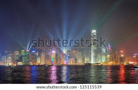 Hong Kong skyline at night with lights and skyscrapers over sea with laser beams - stock photo