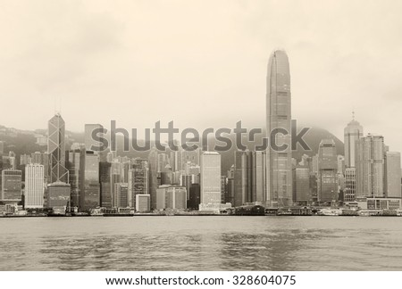 Hong Kong skyline in the morning over Victoria Harbour in black and white.