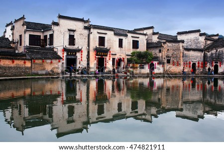 HONGCUN, CHINA - APRIL 20, 2014: Tourist walking around famous Moon Lake in Hongcun Village. Hongcun is ancient village in Anhui Province, near the southwest slope of Mount Huangshan.