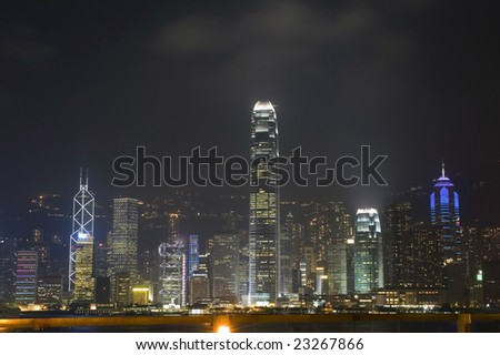 Hongkong cityscape with harbour by night. Modern skyscrapers, offices and hotels in Hongkong Island. View from Kowloon.