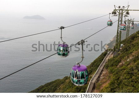 HONGKONG - FEB 04, 2014: Cable cars in Ocean Park, Hongkong on a misty day. Cablecar carries tourists up to the entertainment park. Ocean Park also a center for giant panda breeding.
