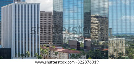 Honolulu, Hawaii, Oct. 1, 2015:  Panorama of the Honolulu Business District with Honolulu Harbor reflected in the building windows.  Honolulu is the business center for the Pacific islands.