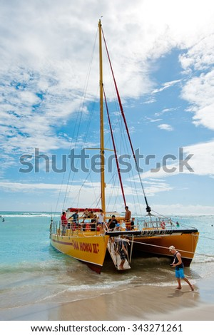 HONOLULU, HAWAII - SEPTEMBER 29, 2012: Catamaran cruise from Waikiki Beach, Hawaii. Unlimited drinks and music while cruising around Oahu make this a popular destination for locals and tourists.