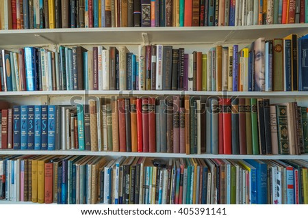 Honolulu, Hawaii, USA, April 13, 2016:  Morning view of a home library with varied subjects and colors on white wooden shelves.   - stock photo