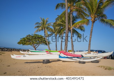 Honolulu, Hawaii, USA, April 5, 2016:  Outrigger canoes at rest under a palm grove in Waikiki on the opening day of Outrigger Canoe Competition.