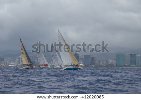 Honolulu, Hawaii, USA, April 27, 2016:  Stormy view of racing sailboats offshore from Waikiki Beach in brisk trade winds.