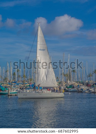 Honolulu, Hawaii, USA, August 1, 2017:  Waikiki evening view of a crew and sailboat maneuvering in the harbor preparing for a sail into the sunset.