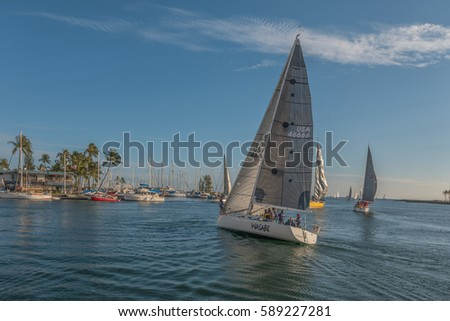 Honolulu, Hawaii, USA, Feb. 27, 2017:  Afternoon view of a racing sailboat on a tack with the Hawaii Yacht Club in the backdrop.