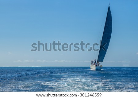 Honolulu, Hawaii, USA, July 29, 2015:  A modern racing sailboat sails into Waikiki's Ala Wai Harbor after a voyage from Los Angeles California.  Long Distance sailing is gaining in popularity.