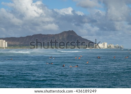 Honolulu, Hawaii, USA, June 13, 2016:  Large surf and expert surfers at Ala Moana Surf Beach in Waikiki with Diamond Head in the background. - stock photo