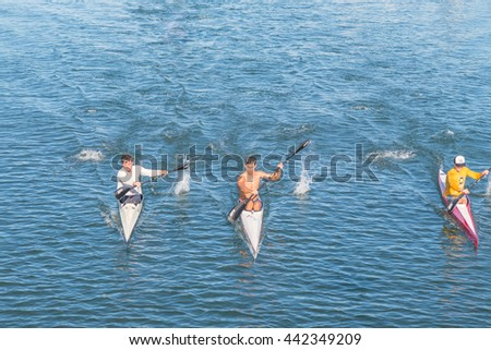 Honolulu, Hawaii, USA, June 24, 2016:  Three kayaks paddling fast up the Ala Moana Channel in the Harbor with blue ocean background.