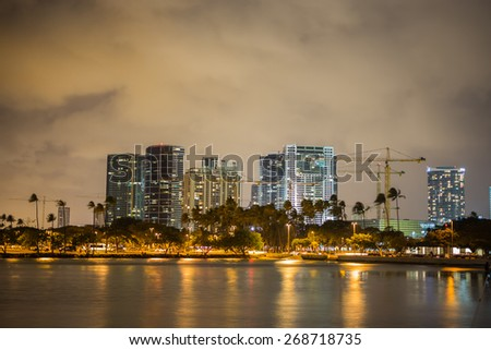 Honolulu, Hawaii, USA, March 31, 2015;  Honolulu construction continues at a record pace in the Ala Moana District of Honolulu under evening rain showers. - stock photo