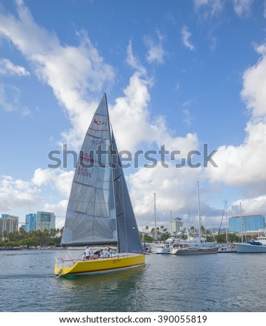 Honolulu, Hawaii, USA, March 13, 2016:  Large racing sailboat and crew tacking through the Ala Wai Harbor with the Waikiki Yacht Club in the background.
