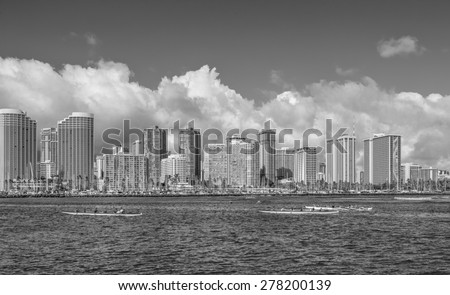 Honolulu, Hawaii, USA, May 15, 2015:  Honolulu and Waikiki in the background while outrigger canoes practice for the State of Hawaii Canoe Championships. - stock photo