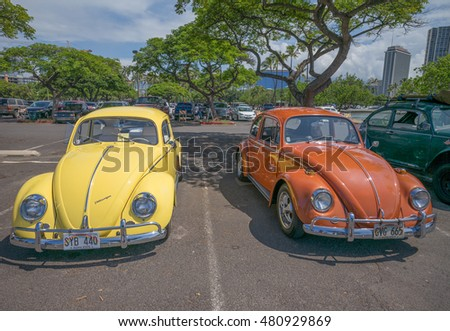 Honolulu, Hawaii, USA, Sept. 9, 2016:  Yellow, orange, and green restored cars at the beach in Waikiki with partly cloudy skies above.