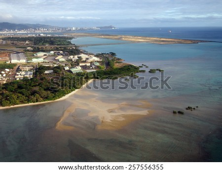 Honolulu International Airport and Coral reef Runway seen from the air with surrounding water and Honolulu city in the distance on Oahu, Hawaii.  - stock photo
