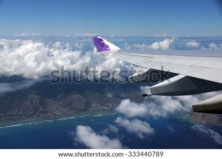 HONOLULU, JUNE 26: Wing of Hawaiian Airlines plane flying in the air above Honolulu, Hawaii and clouds on June 26, 2015. - stock photo