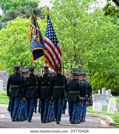 Honor Guard  carrying flags marching to a burial at Arlington National Cemetery - stock photo