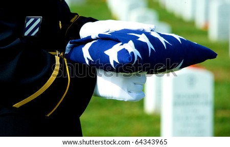 Honor Guard holding folded American flag at grave site at Arlington National Cemetery - stock photo