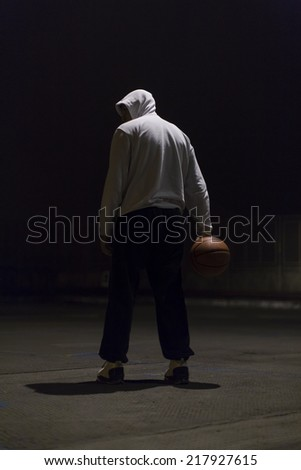 Hooded basketball player holding a basketball in one hand and standing in a dimly lit environment - stock photo