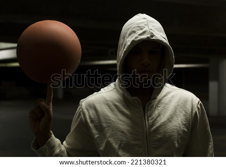 Hooded basketball player spinning the ball under a light in the darkness. Sports concept with very shallow depth of field and motion blur of the ball spinning - stock photo